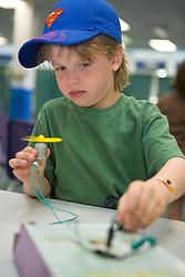 United States, Washington, Bellevue, KidsQuest Children's Museum, boy with electric propeller he built