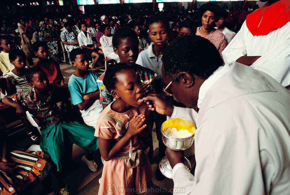 The bells of Regina Mundi Church ring out, calling the faithful to Soweto's largest Roman Catholic Church for Sunday service, where they receive communion. Published in Material World on page 26. South Africa.