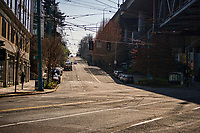 A lone jogger heads towards the incline of Harvard Avenue away from what is typically a very busy intersection of cars, buses, bikes, and pedestrians in the Eastlake neighborhood. (March 21, 2020)