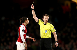 Arsenal's Hector Bellerin receives a yellow card from Referee Pavel Kralovec for unsporting behaviour