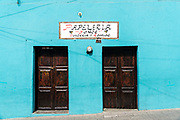 A aqua blue wall and wooden doors in Angangueo, Michoacan, Mexico. Angangueo is a tiny, remote mountain town and the entry point to the Sierra Chincua Monarch Butterfly Sanctuary.