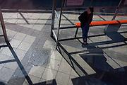 London bus passenger waits at a Waterloo bus stop.