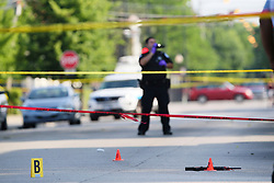 A weapon lies in the middle of the 1300 block of South Loomis Street while an evidence technician from the Chicago Police Department gathers images from the scene of a shooting near South Loomis Street and West 13th Street on Monday. Photo by Joe Cavaretta/Sun Sentinel/TNS/ABACAPRESS.COM