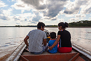 A family heads to the mining corridor in Madre de Dios, Peru.