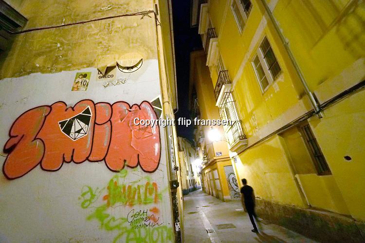 Spanje, Valencia, 3-11-2019  Beeld uit de oude, historische, binnenstad, stedscentrum van deze spaansen stad . In een steeg loopt een man, bewoner . Er is graffiti op de muur geschiderd .Foto: Flip Franssen