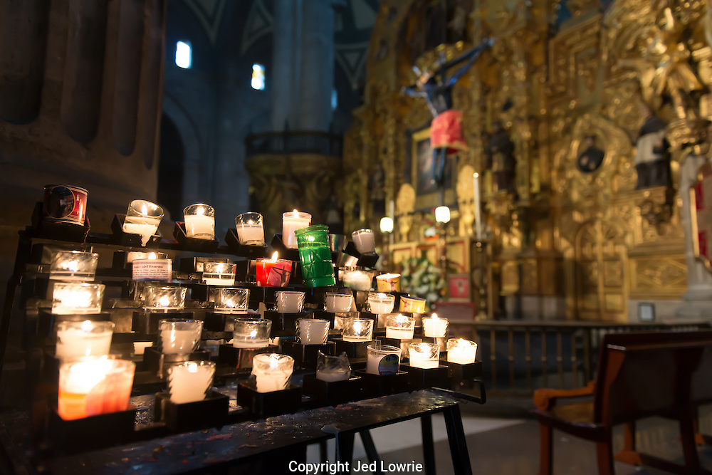 Candles are lit inside of the Cathedral off of the Zocalo in Mexico CIty.  The Cathedral is very ornate with many gold leaf alters.