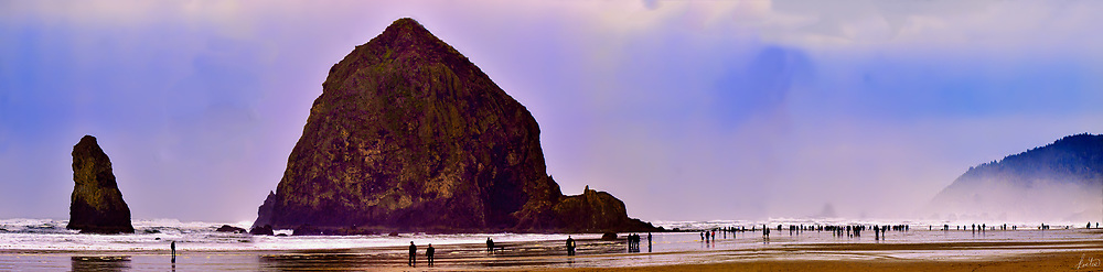 Haystack Rock at Cannon Beach on a Thanksgiving Day with lots of folks enjoying the misty conditions.