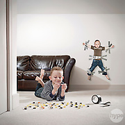 Two young brothers fighting over sweets with the older boy winning by taping his sibling to the wall and claiming the haul of sweets for himself.