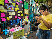 """06 JULY 2015 - BANGKOK, THAILAND:  A person writes a """"Post It"""" note in support of arrested university students during a protest at Thammasat University. More than 100 people gathered at Thammasat University in Bangkok Monday to show support for 14 students arrested two weeks ago. The students were arrested for violating orders against political assembly. They face criminal trial in military courts. The students' supporters are putting up """"Post It"""" notes around Bangkok and college campuses up country calling for the students' release.     PHOTO BY JACK KURTZ"""
