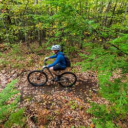 A man mountain biking in the Raymond Community Forest in Raymond, Maine. Fall.