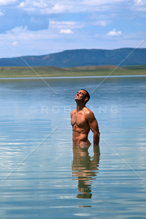 naked man enjoying the feel of the sun while standing in a beautiful lake in New Mexico