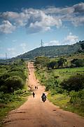 Motorbike drives along dirt road track past walking pedestrians on their way to Mbulu, Manyara district, Tanzania, East Africa.