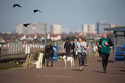 © Licensed to London News Pictures.27/03/2021. Southend-On-Sea,UK. Members of the public walk past the Thames Estuary in Southend-on-Sea, Essex. The weather forecasts predict sunny weather with strong winds in the southeast England.`Photo credit: Marcin Nowak/LNP