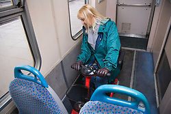 Woman parking electric mobility scooter on a train carriage,