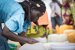 30 May 2019, Mokolo, Cameroon: 25-year-old Nigerian refugee Mariamou Bitrus cleans her buckets by one of the tapstands in Minawao camp, where she arrived in 2014. The Minawao camp for Nigerian refugees, located in the Far North region of Cameroon, hosts some 58,000 refugees from North East Nigeria. The refugees are supported by the Lutheran World Federation, together with a range of partners.