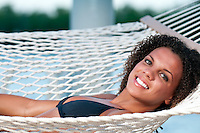 Young woman resting in a hammock with marine background