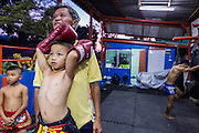 """18 DECEMBER 2104 - BANGKOK, THAILAND: A boy who wants to box watches a sparring session at the Kanisorn gym. The Kanisorn boxing gym is a small gym along the Wong Wian Yai - Samut Sakhon train tracks. Young people from the nearby communities come to the gym to learn Thai boxing. Muay Thai (Muai Thai) is a Thai fighting sport that uses stand-up striking along with various clinching techniques. It is sometimes known as """"the art of eight limbs"""" because it is characterized by the combined use of fists, elbows, knees, shins, being associated with a good physical preparation that makes a full-contact fighter very efficient. Muay Thai became widespread internationally in the twentieth century, when practitioners defeated notable practitioners of other martial arts. A professional league is governed by the World Muay Thai Council. Muay Thai is frequently seen as a way out of poverty for young Thais and Muay Thai camps and schools are frequently crowded. Muay Thai professionals and champions are often celebrities in Thailand.     PHOTO BY JACK KURTZ"""