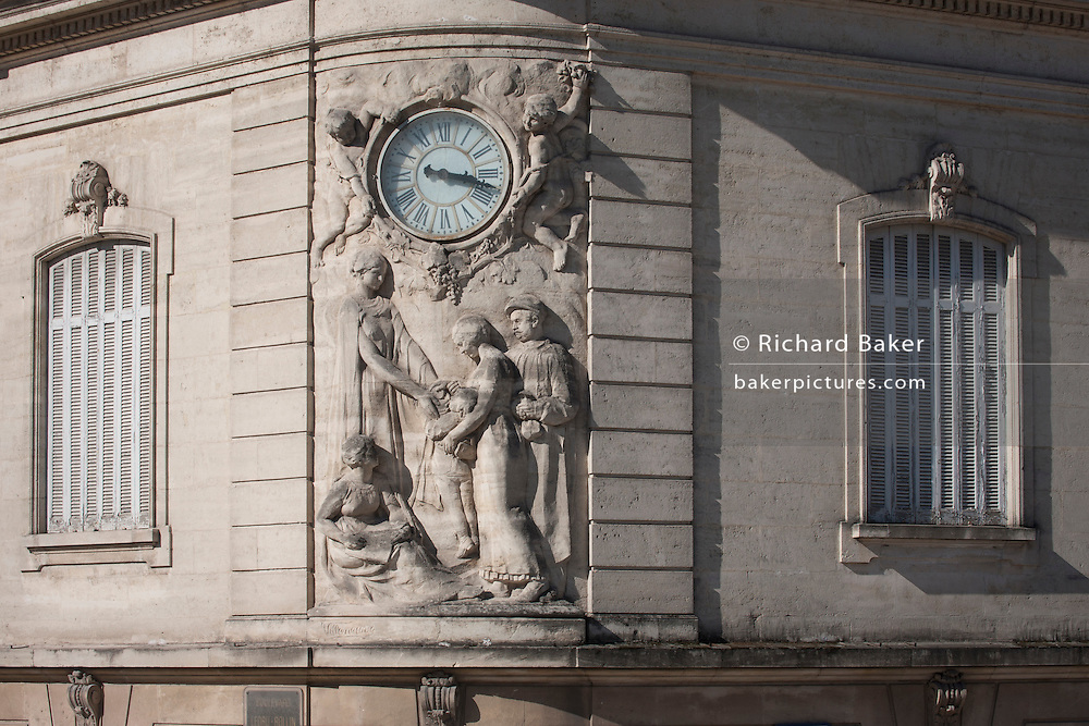 Ornate reliefs and clockface on the exterior of the Caisse D'Epargne bank on Boulevard Ledru Rollin, Montpellier, south of France.