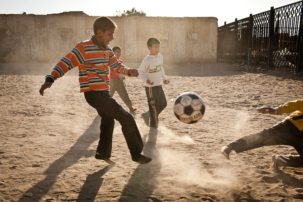 Children play soccer in an empty lot on Haifa Street where a building that was destroyed by American bombing in the Iraq War once stood.