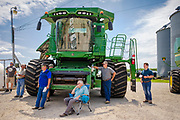 """06 AUGUST 2020 - FAIRFIELD, IOWA: People use the shade of a combine that was being auctioned off to watch the bidding during the auction on the Adam Farm near Fairfield. Gary Adam, 72 years old, has been farming in the Fairfield area since 1971. He decided to retire this year because he wants to travel and because it's so difficult to make money in farming this year. He said he wants to """"shed the risk and responsibility. If things were super good, like they were 2006-2012, I might stay in it, but they're not."""" An increasing number of farmers in the Midwest are retiring this year as it becomes harder to make money on crops. In addition to low prices, Iowa farmers are being hit with a drought this year, with well below average rain over most of the state. Because of the COVID-19 pandemic, the auction on Adam's farm was one of the first live in person auctions since winter. Most auctions are now done on line.    PHOTO BY JACK KURTZ"""