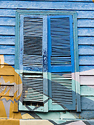 """Louvered window shutters are painted blue and green in San Telmo barrio, the heart of old Buenos Aires, Argentina, South America. Admire well-preserved buildings in San Telmo (""""Saint Pedro González Telmo""""), the oldest barrio (neighborhood) of Buenos Aires, in Argentina, South America."""