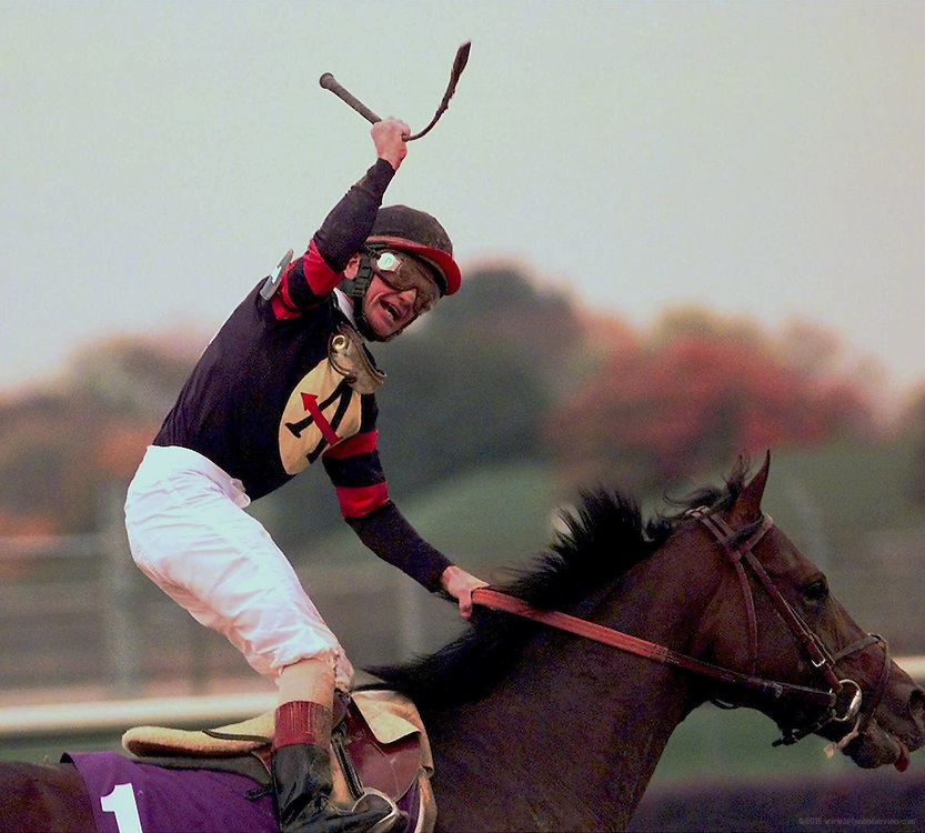 Jockey Pat Day hoists his riding crop into the air after guiding Awsome Again to victory in the Breeders' Cup Classic, Saturday, Nov. 7, 1998, at Churchill Downs in Louisville, Ky.  Silver Charm ran second and Swain finished third.  (AP Photo/Brian Bohannon)