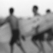 Selective focus, black and white, grainy image of three surfers walking to the surf carrying their surfboards.