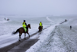 © Licensed to London News Pictures. 12/04/2021. Epsom, UK. Horses exercise as snow hits Epsom Racecourse in Surrey. Unusually late spring snow is hitting parts of the UK today as lockdown restrictions are being eased today.  Photo credit: Peter Macdiarmid/LNP