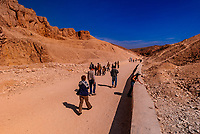 Tourists walking between the tombs of the Valley of the Kings Archaeological site, near Luxor, Egypt