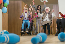 Girls playing bowling with senior woman in rest home