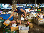 04 JANUARY 2016 - BANGKOK, THAILAND:  A vendor cleans out his stall in Bang Chak Market after the market closed permanently. The market closed January 4, 2016. The Bang Chak Market serves the community around Sois 91-97 on Sukhumvit Road in the Bangkok suburbs. About half of the market has been torn down. Bangkok city authorities put up notices in late November that the market would be closed by January 1, 2016 and redevelopment would start shortly after that. Market vendors said condominiums are being built on the land.       PHOTO BY JACK KURTZ