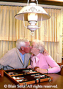 Active Aging Senior Citizens, Retired, Activities, Elderly Couple Play Table Game at Home, Kissing Couple