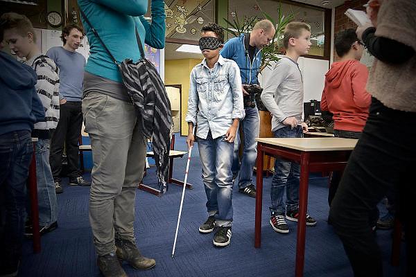 Nederland, Ede, 14-11-2013Op de Franciscus basisschool ervaren leerlingen hoe het is om een beperking te hebben, bijvoorbeeld blind of doof. Met een kaartje waar gebarentaal op staat en een koptelefoon op proberen ze te communiceren. Met een blinddoek en blindenstok moeten ze hun weg vinden.Foto: Flip Franssen/Hollandse Hoogte