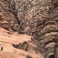 A climber scrambles on strangely eroded sandstone in Rakabat Canyon, Jebel Um Ishrin, Wadi Rum, Jordan.