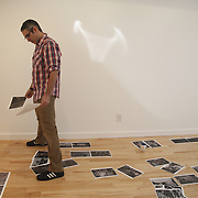 Louie Palu editing for 2nd floor installation of laser prints from the Fighting Season body of work hanging in the Honfleur Gallery in 2011 in Washington DC
