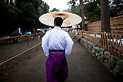 KAMAKURA, JAPAN, 16 SEPTEMBER - a Kannushi wearing a purple hakama and a white kimono, under the rain with a traditional umbrella. A Kannushi or Shinshoku is a person who have responsabilities in a shinto shrine and can profess ceremonies. Tsurugaoka Hachimangu  the most important temple of Kamakurawas founded 1063 and inlarge by Minato Yorimoto, the first Shogun of Kamakura period - september 2012