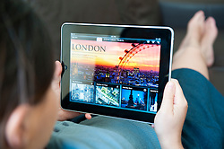 close up of woman using iPad digital tablet computer to read illustrated travel ebook to London