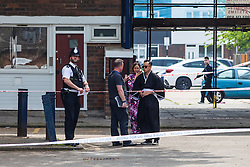 28/05/2016. London, UK. Two local residents, on their way to Comic Con, speak with police investigators after a boy was stabbed 'repeatedly' on Payne Street in Deptford, south London. The 16-year-old victim is said to be in a 'critical' condition, and a police cordon remains in place as investigations continue. Photo credit: Rob Pinney