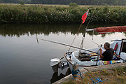 With rods over the deck of his small yacht, a man fishes for perch on the still waters of the river Chet, on 13th August 2020, in Loddon, Norfolk, England.