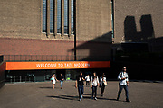 Visitors outside Tate Modern gallery of contemporary art in London, England, United Kingdom. Tate Modern is based in the former Bankside Power Station in Southwark and is one of the largest museums of modern and contemporary art in the world. As with the UKs other national galleries and museums, there is no admission charge for access to the collection displays, which take up the majority of the gallery space. The redevelopment of the space was undertaken by architects Herzog & de Meuron.