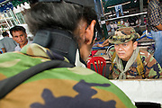 """May 12 - BANGKOK, THAILAND: Maj. Gen. KHATTIYA """"Seh Daeng"""" SAWASDIPOL (RIGHT) talks to a Red Shirt security official at a Red Shirt barricade in the Red Shirt camp in Bangkok Wednesday. Seh Daeng, as he is known, has emerged as the Red Shirts unofficial military commander. He has organized the barricades that ring the Red Shirt camp and has threatened to organize a guerilla campaign against the government if the Red Shirt protest is crushed by force. Seh Daeng is a hero to many Thais because he is credited with crushing Thailand's communist insurgency in the 1970's and 80's. He was the commander of Thailand's Internal Security Operations Command but after his political activities became apparent he was made the head aerobics instructor for the Thai army. He is now seen as one of the major personalities destabilizing the country and the government alleges that he is behind many of the grenade attacks and drive by shootings directed at government buildings and officials and he is wanted for a long list of felony offenses including weapons charges and terrorism related charges. Although some Red Shirts have officially repudiated him, he is still frequently seen around the Reds' barricades. The army has started proceedings to fire him, but he remains a general on active duty. Photo by Jack Kurtz"""