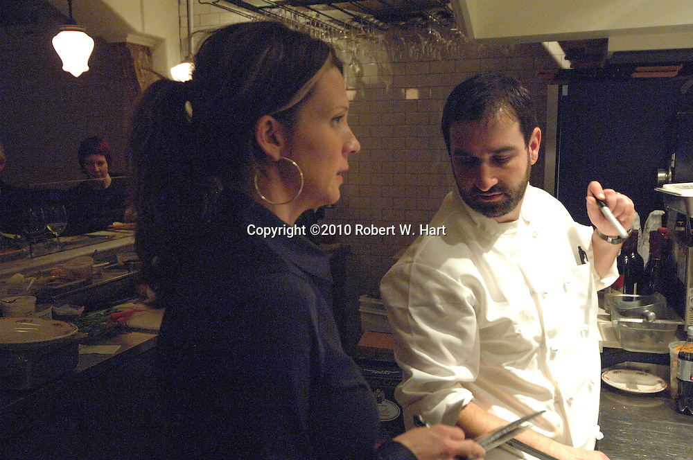 Waitress Stephanie Andrus confers with Lucia restaurant owner and chef, David Uygur, outside the kitchen Tuesday evening Dec. 14, 2010 at 408 W. 8th. St., in the Bishop Arts District of Dallas' Oak Cliff neighborhood.