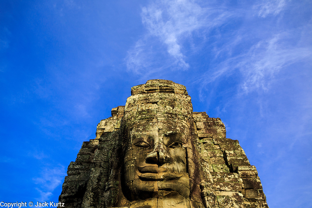 """02 JULY 2013 - ANGKOR WAT, SIEM REAP, SIEM REAP, CAMBODIA:  Stone heads in Bayon, one of the temples in the Angkor Wat complex. Angkor Wat is the largest temple complex in the world. The temple was built by the Khmer King Suryavarman II in the early 12th century in Yasodharapura (present-day Angkor), the capital of the Khmer Empire, as his state temple and eventual mausoleum. Angkor Wat was dedicated to Vishnu. It is the best-preserved temple at the site, and has remained a religious centre since its foundation– first Hindu, then Buddhist. The temple is at the top of the high classical style of Khmer architecture. It is a symbol of Cambodia, appearing on the national flag, and it is the country's prime attraction for visitors. The temple is admired for the architecture, the extensive bas-reliefs, and for the numerous devatas adorning its walls. The modern name, Angkor Wat, means """"Temple City"""" or """"City of Temples"""" in Khmer; Angkor, meaning """"city"""" or """"capital city"""", is a vernacular form of the word nokor, which comes from the Sanskrit word nagara. Wat is the Khmer word for """"temple grounds"""", derived from the Pali word """"vatta."""" Prior to this time the temple was known as Preah Pisnulok, after the posthumous title of its founder. It is also the name of complex of temples, which includes Bayon and Preah Khan, in the vicinity. It is by far the most visited tourist attraction in Cambodia. More than half of all tourists to Cambodia visit Angkor.         PHOTO BY JACK KURTZ"""
