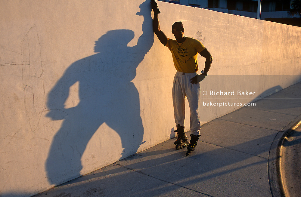 An athletic man poses against a wall on Ocean Drive in Miami Beach, Florida. This fine specimen of a man wears roller-blades and trousers tucked into his skates with a yellow t-shirt with the word Frequency across his pectoral muscles. His shdow appears across the wall and because of the angle, his shape has been greatly exaggerated, his body becoming a much wider, stockier proportion than the reality. He stands with an arm resting high on the wall and the other on his hip, almost in a feminine manner. He is nonetheless the epitome of maleness, of virility with the healthy physique that women adore and other men are jealous of! The sdidewalk pavement arcs around a corner and the wall with its long shadow is a strong diagonal line across the picture, disappearing to the far right.