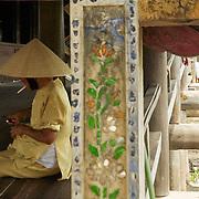 Vietnamese woman smoking at bridge