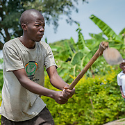 CAPTION: SignHealth Uganda often uses its volunteers to put on short dramas at events in order to heighten awareness and challenge the stigmas attached to hearing impairment. In this scene, a boy is performing manual labour in the fields. This is a common occurrence among hearing impaired children, whose parents are embarrassed by them and force them to do hard work instead of sending them to school. LOCATION: Kakunyu Inclusive Nursery and Primary School, Kakunyu Village, near Masaka city, Lweongo District, Central Region, Uganda. INDIVIDUAL(S) PHOTOGRAPHED: Geoffrey Kalanzi.