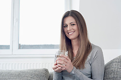 Portrait of smiling young woman holding glass of water