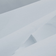 Layers of snow and ice form gentle shapes on the slopes of a mountain at Melvhior Island on the western side of the Antarctic Peninsula. The snow is set against gray clouds in the top left corner.