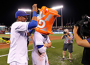 Kansas City Royals' Salvador Perez, left, puts a bucket on the head of Kansas City Royals'  Mike Moustakas after dunking him with water after a baseball game New York Yankees at Kauffman Stadium in Kansas City, Mo., Friday, May 15, 2015. The Royals beat the Yankees 12-1. (AP Photo/Colin E. Braley)