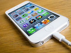 using white iPhone 5 smartphone with cable attached